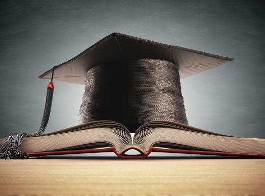 Afstudeerhoed ligt op boek.