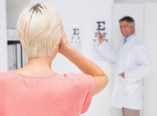 opticien neemt oogtest af