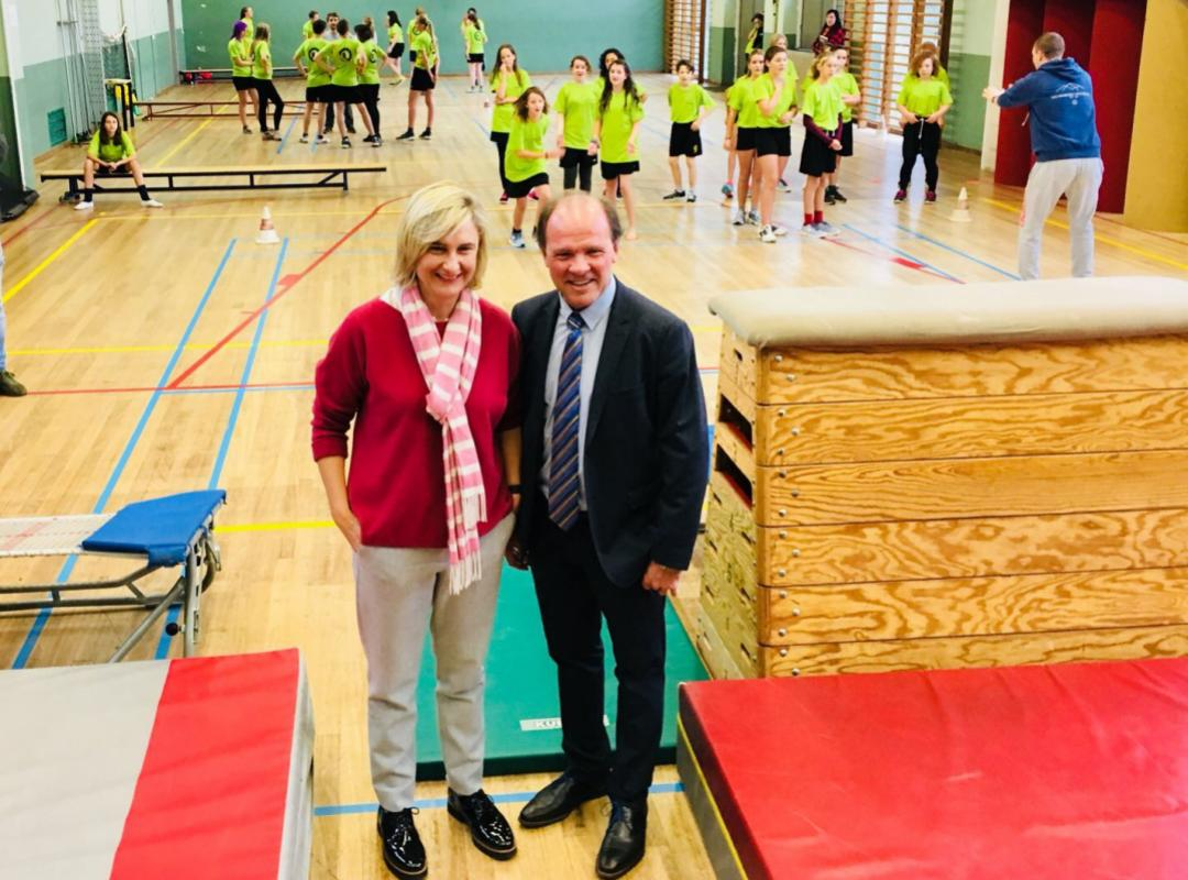 Philippe Muyters en Hilde Crevits in sporthal met sportende kinderen